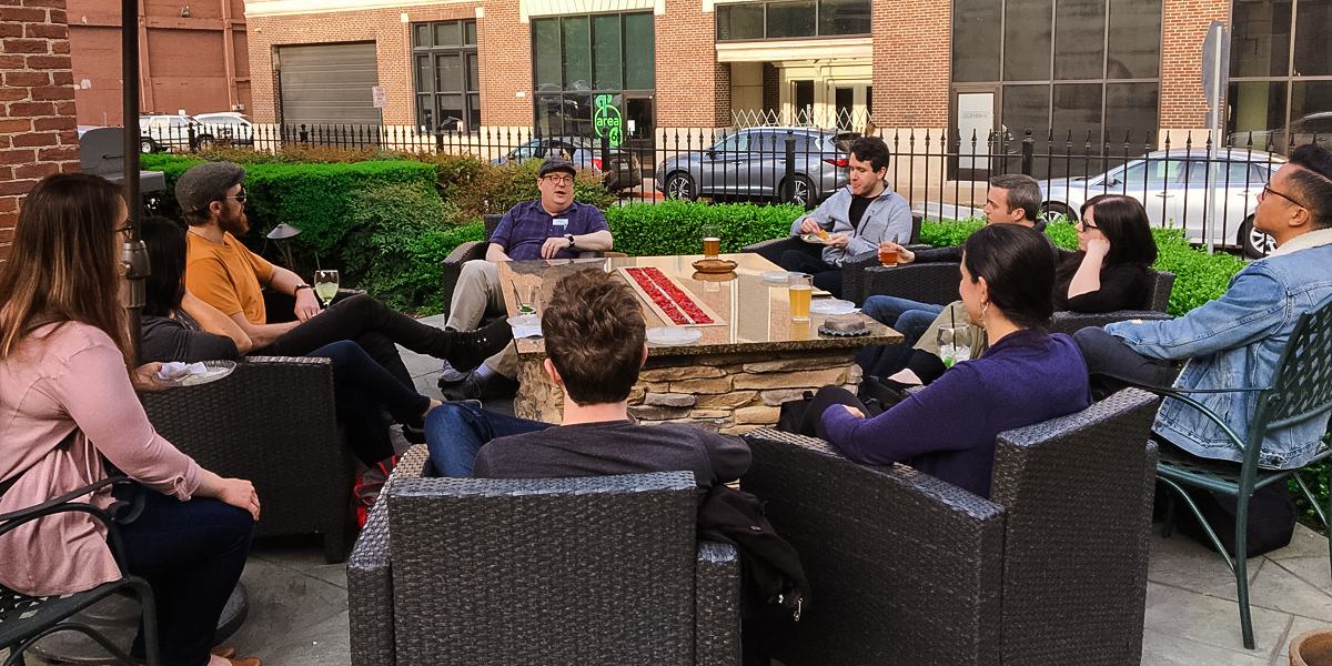 Photo of Jared on an outdoor patio surrounded by workshop attendees during the workshop Happy Hour.